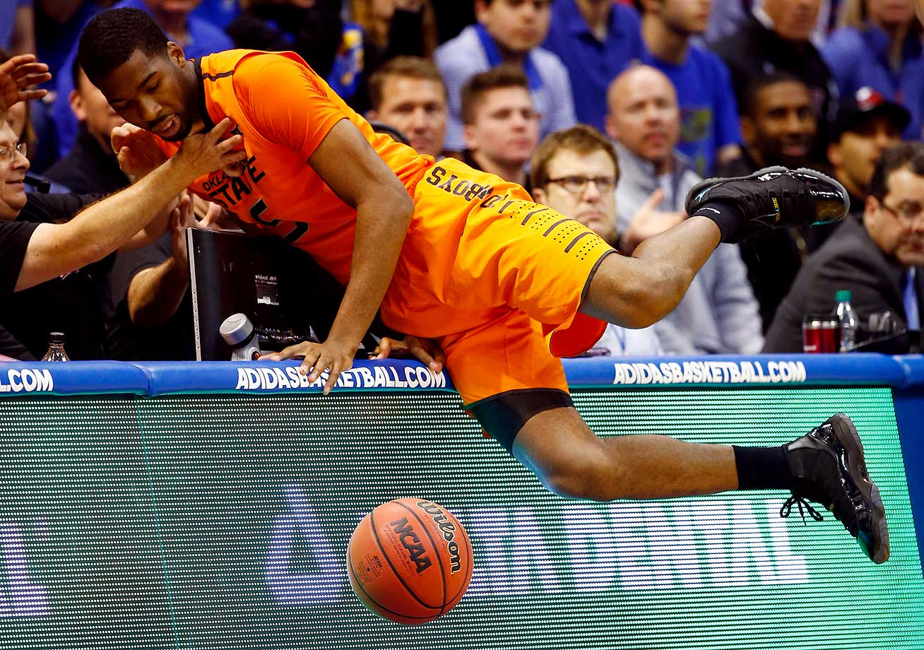 Tavarius Shine of Oklahoma State dives into the crowd to try to save a loose ball against Kansas.