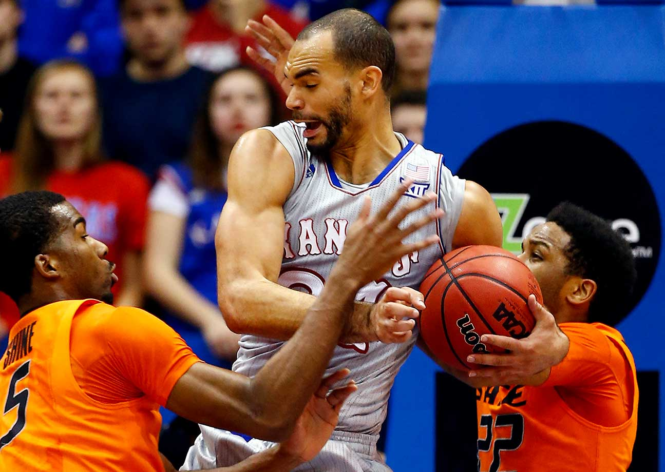 Perry Ellis controls the ball as Tavarius Shine, left, and Jeff Newberry of Oklahoma State defend.