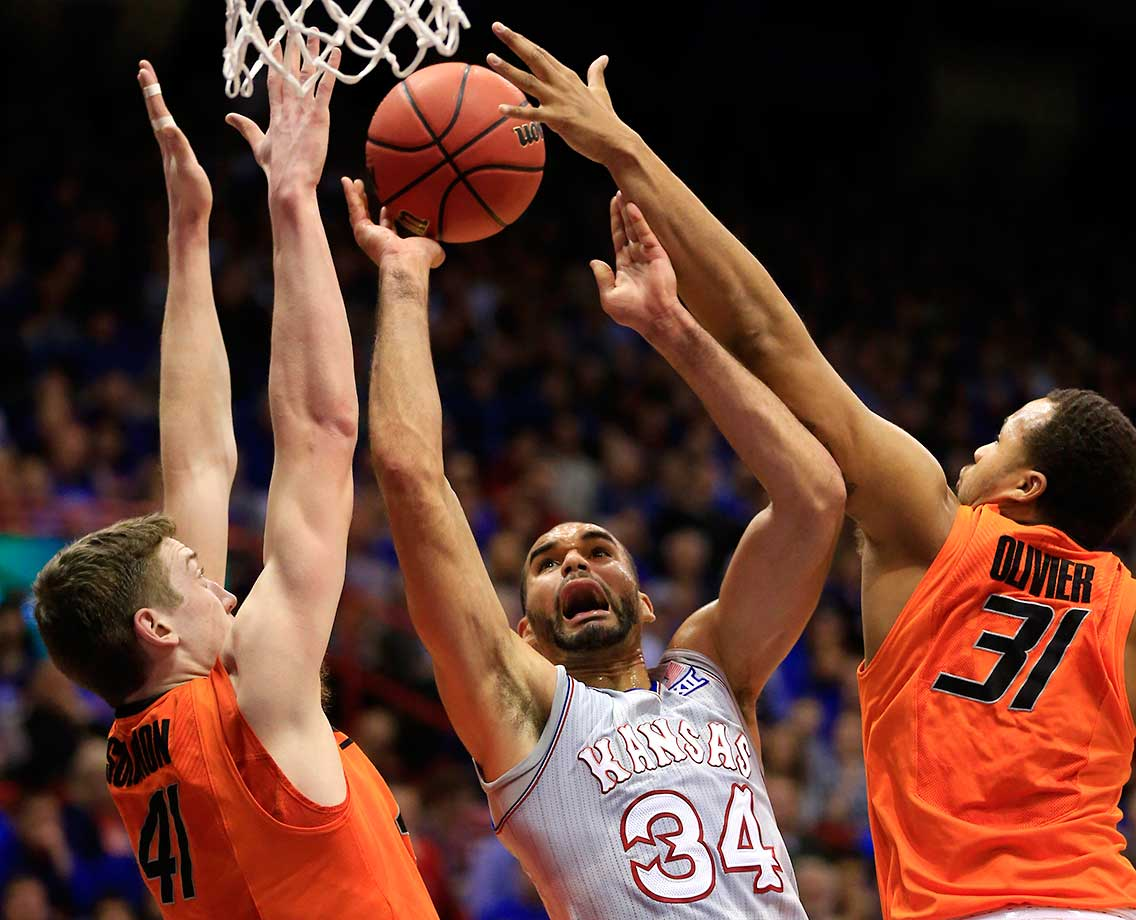 Kansas forward Perry Ellis shoots while covered by Oklahoma State's Mitchell Solomon (41) and Chris Olivier.
