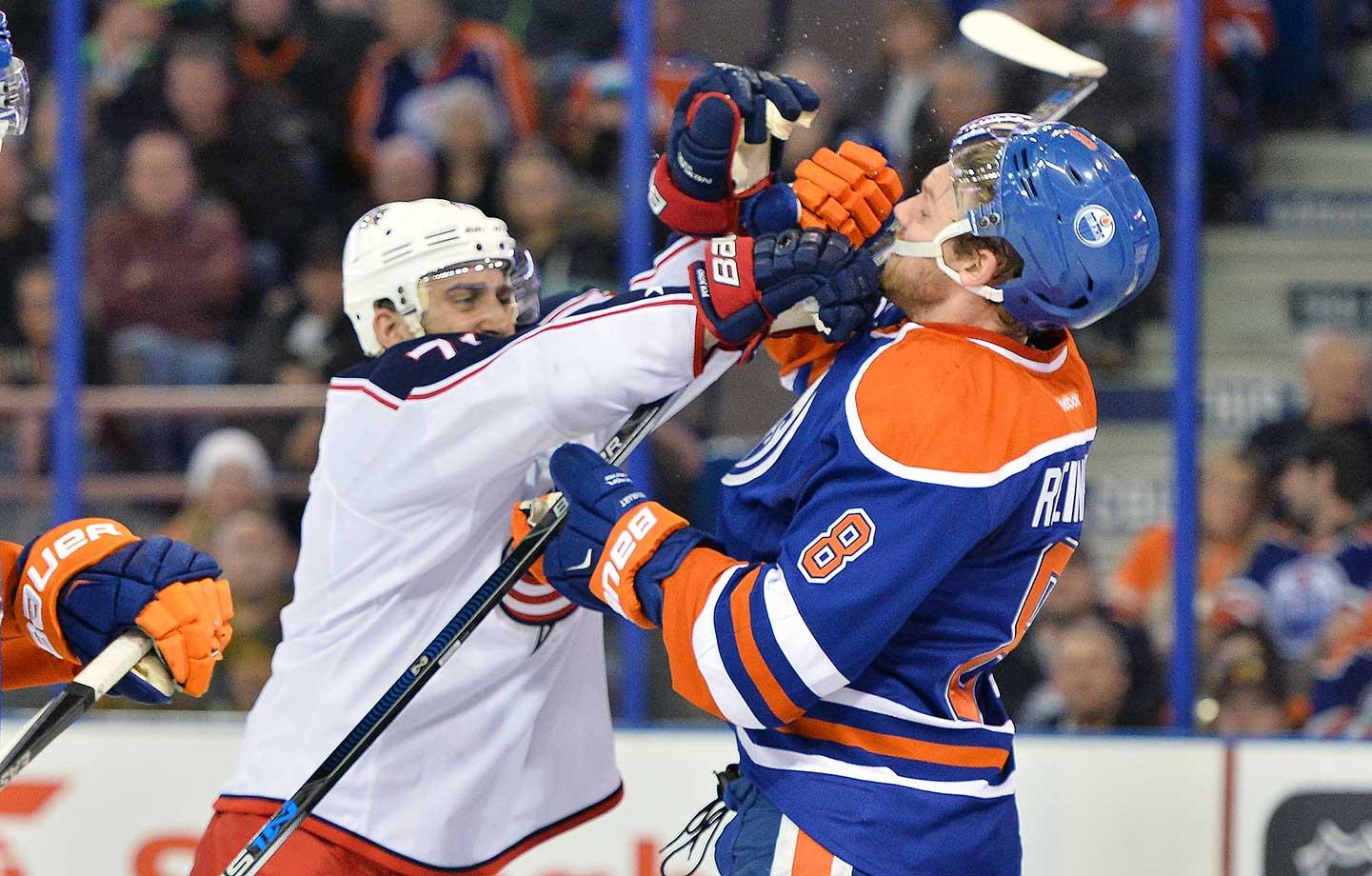 Columbus Blue Jackets winger Nick Foligno punches Edmonton Oilers defenseman Griffin Reinhart at Rexall Place in Edmonton, Alberta, Canada.