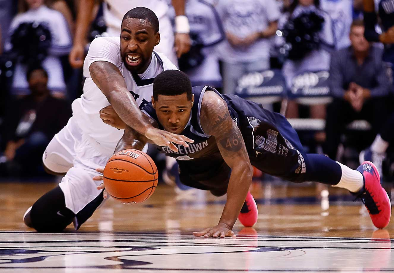 Roosevelt Jones of the Butler Bulldogs and D'Vauntes Smith-Rivera of the Georgetown Hoyas dive for a loose ball at Hinkle Fieldhouse in Indianapolis. Butler defeated Georgetown 87-76.