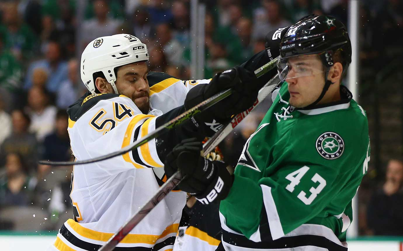 Adam McQuaid of the Boston Bruins delivers a blow to Valeri Nichushkin of the Dallas Stars.
