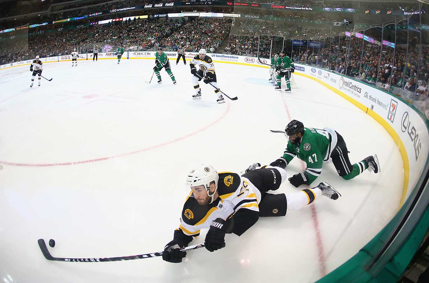 Landon Ferraro of the Boston Bruins skates the puck against Johnny Oduya of the Dallas Stars.