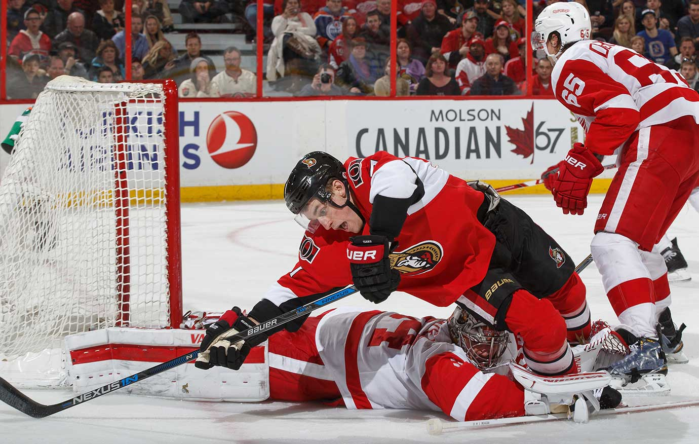 Kyle Turris of the Ottawa Senators collides with Petr Mrazek of the Detroit Red Wings outside his crease.