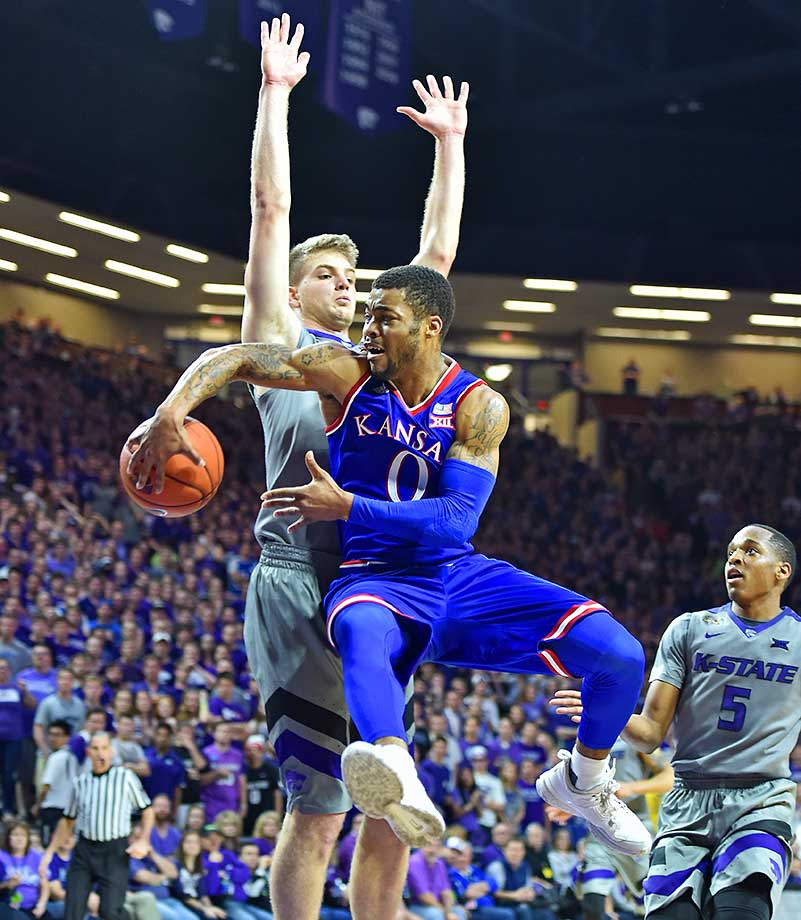 Guard Frank Mason III of Kansas passes around Dean Wade of the Kansas State Wildcats.