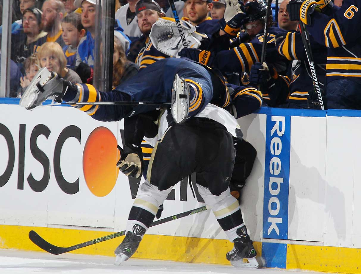 Nicolas Deslauriers of Buffalo is upended as Sidney Crosby of the Pittsburgh Penguins ducks his check.