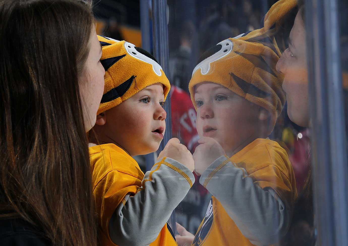 A young fan watches from the glass as the Buffalo Sabres play the Pittsburgh Penguins on Hockey Day in America.