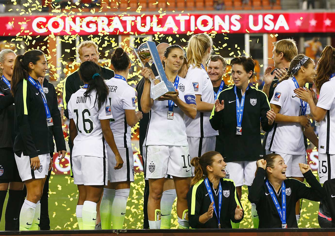 U.S. Captain Carli Lloyd poses on stage with teammates after they beat Canada 2-0.