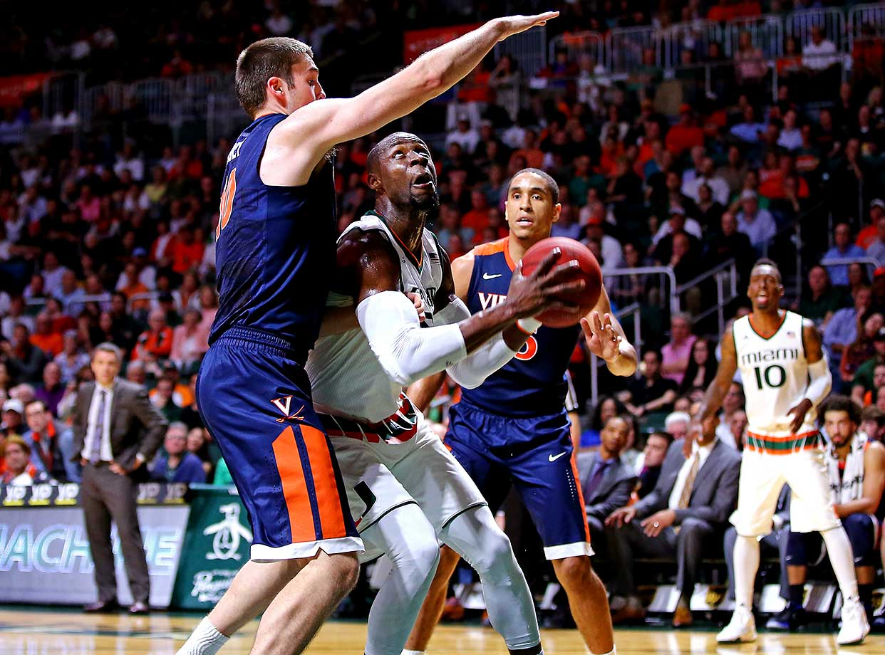 Tonye Jekiri of the Miami Hurricanes is defended by Mike Tobey of the Virginia Cavaliers.