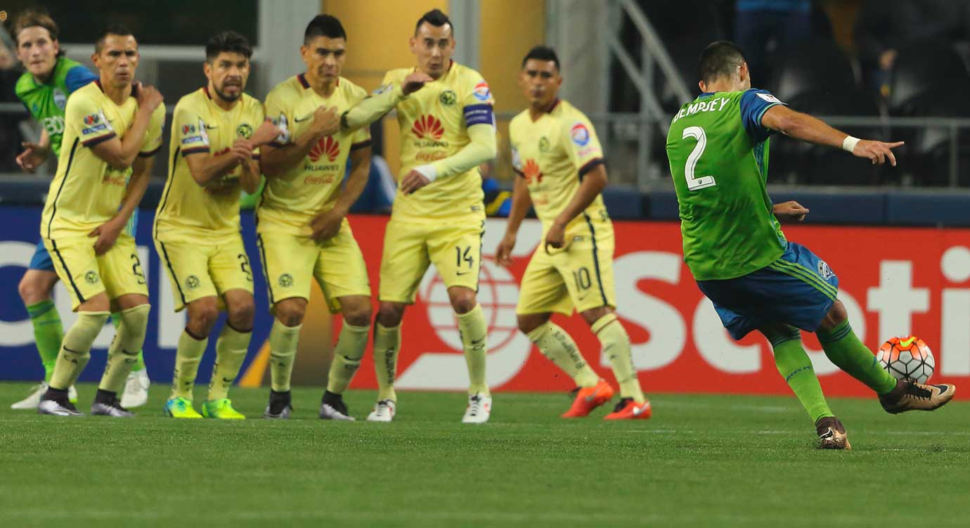Club America players cover up as Clint Dempsey of the Seattle Sounders scores on a free kick during a CONCACAF Champions League match.