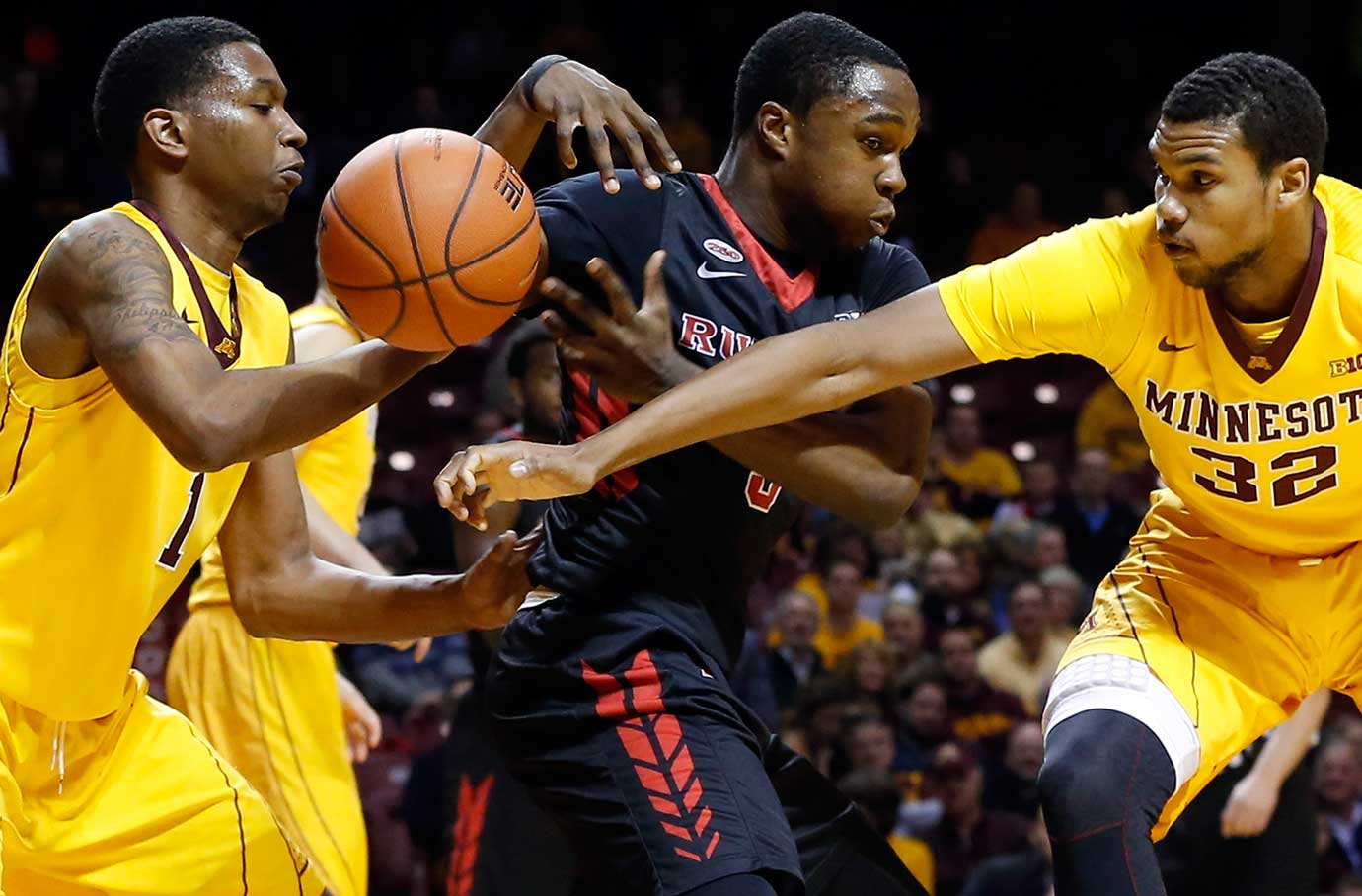 Mike Williams of Rutgers loses the ball as Minnesota's Dupree McBrayer, left, and Ahmad Gilbert Jr. defend.