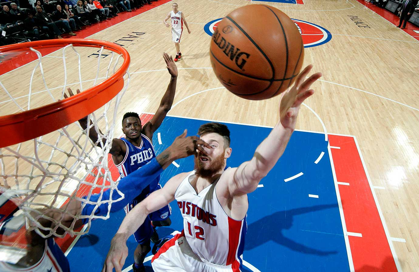 Aron Baynes of the Detroit Pistons appears to get poked in the face while shooting against Philadelphia.