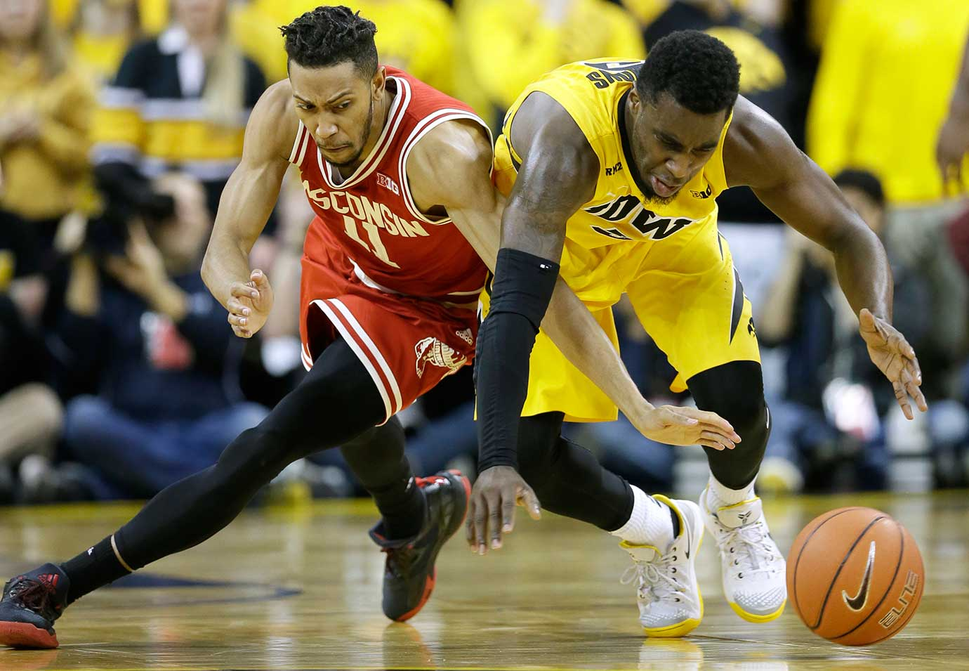 Wisconsin guard Jordan Hill fights for a loose ball with Iowa guard Anthony Clemmons.
