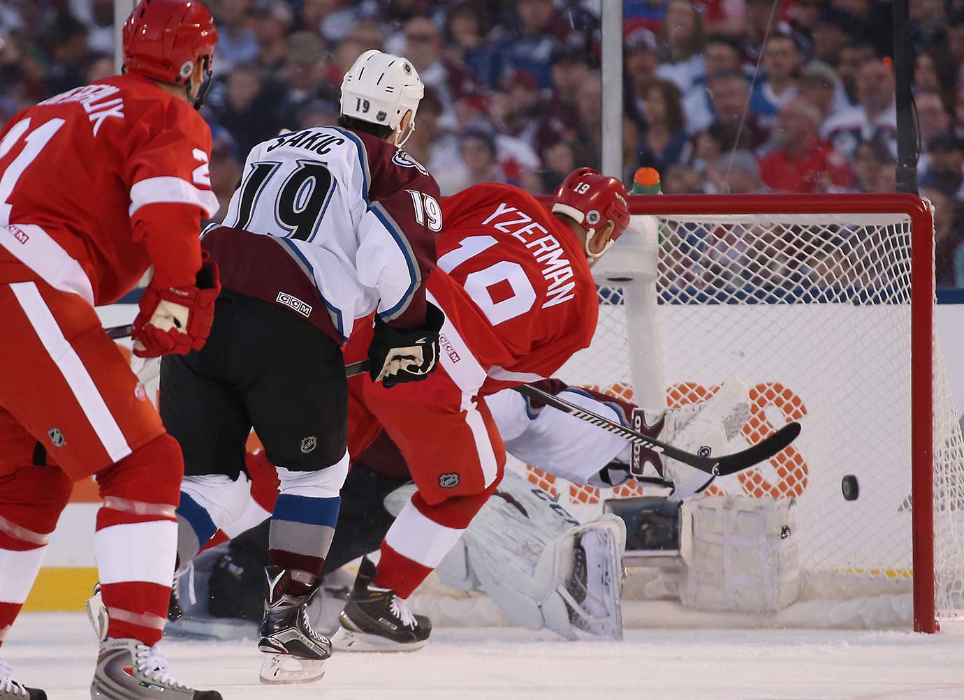 Steve Yzerman of the Red Wings Alumni team scores against Patrick Roy in Denver.
