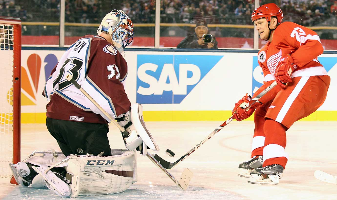 Patrick Roy of the Colorado Avalanche Alumni team makes a body save against Stacy Roest.