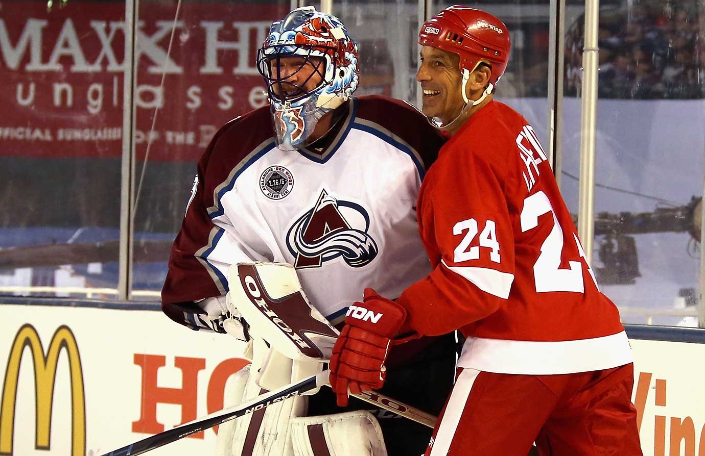 Patrick Roy of the Avalanche Alumni and Chris Chelios of the Red Wings Alumni share a laugh.