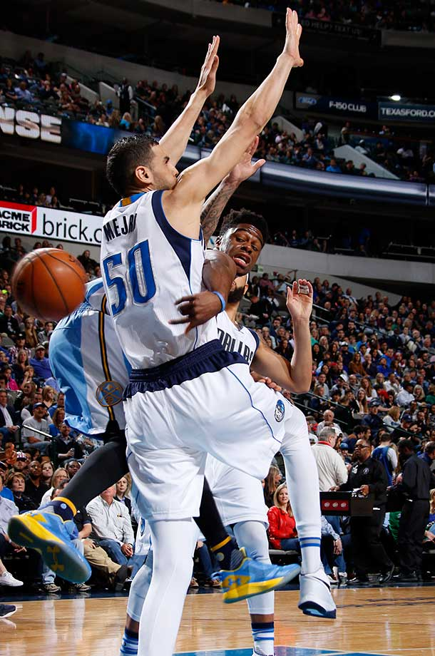 Emmanuel Mudiay of the Denver Nuggets wraps a pass around Salah Mejri of the Dallas Mavs.