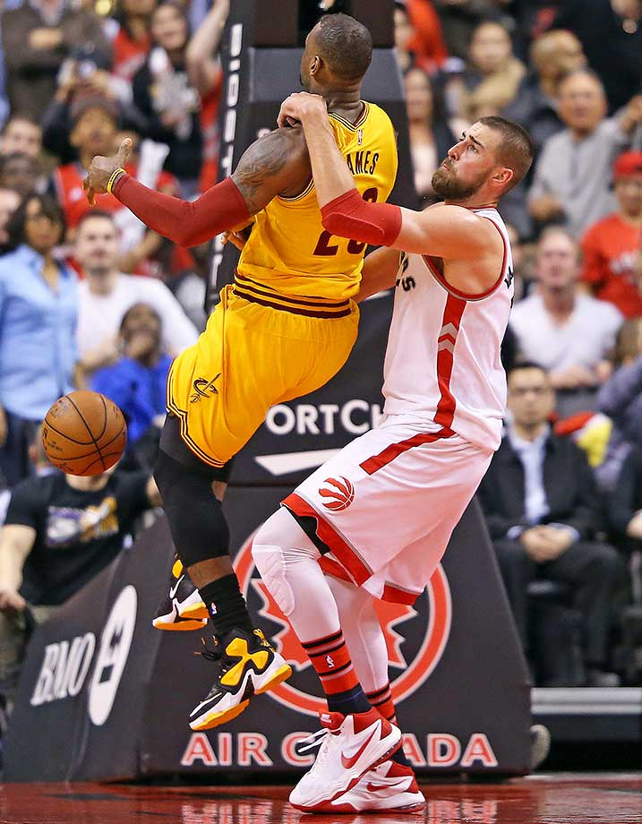 Jonas Valanciunas of Toronto draws a foul by pulling down LeBron James of the Cavs.
