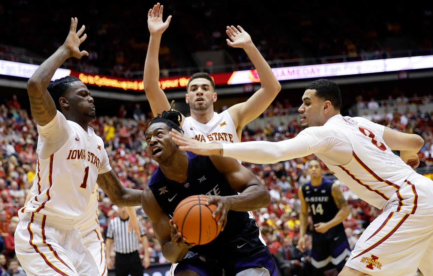 Kansas State's D.J. Johnson is defended by Iowa State's Jameel McKay, left, Georges Niang, rear, and Abdel Nader.