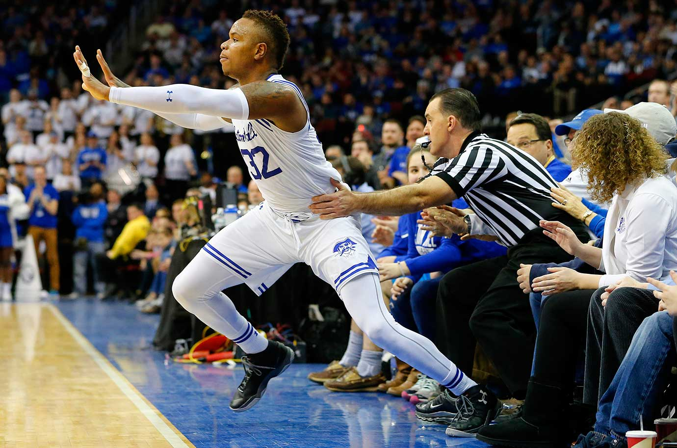 Derrick Gordon of Seton Hall is pushed back onto the court by an official after both landed in the front row of seats against Xavier.