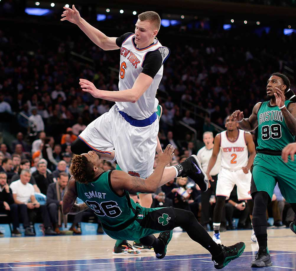 New York Knicks forward Kristaps Porzingis runs over Boston Celtics guard Marcus Smart after putting up a shot in New York. Porzingis was called for an offensive foul on the play.