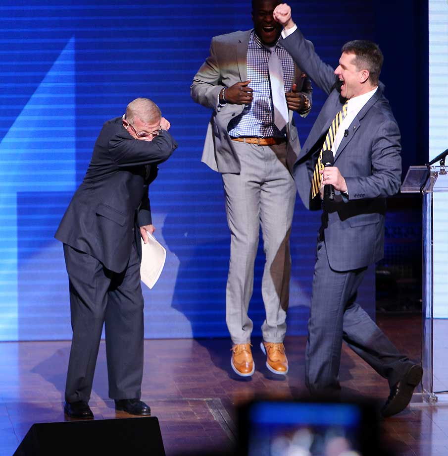 Lou Holtz, former Notre Dame head coach, dabs in front of Michigan coach Jim Harbaugh during the Michigan Signing of the Stars event .