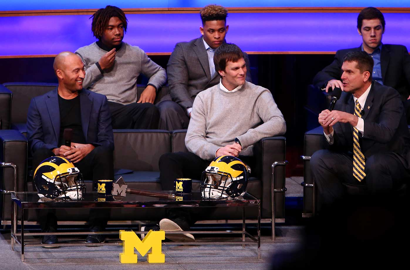 Derek Jeter and Tom Brady talk with Michigan coach Jim Harbaugh during the Michigan Signing of the Stars event at Hill Auditorium in Ann Arbor, Mich.
