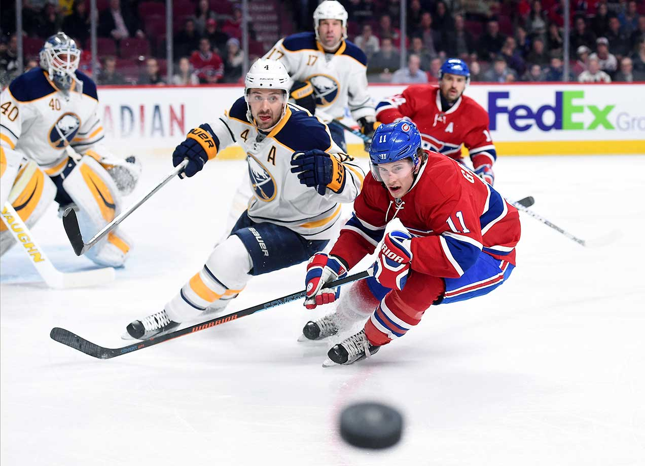 Brendan Gallagher of the Montreal Canadiens and Josh Gorges of the Buffalo Sabres skate for the puck at the Bell Centre in Quebec.