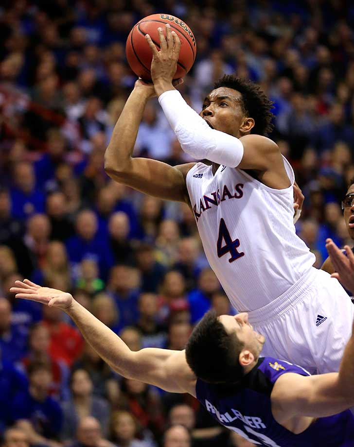 Kansas guard Devonte' Graham is fouled by Kansas State guard Brian Rohleder in Lawrence, Kan.
