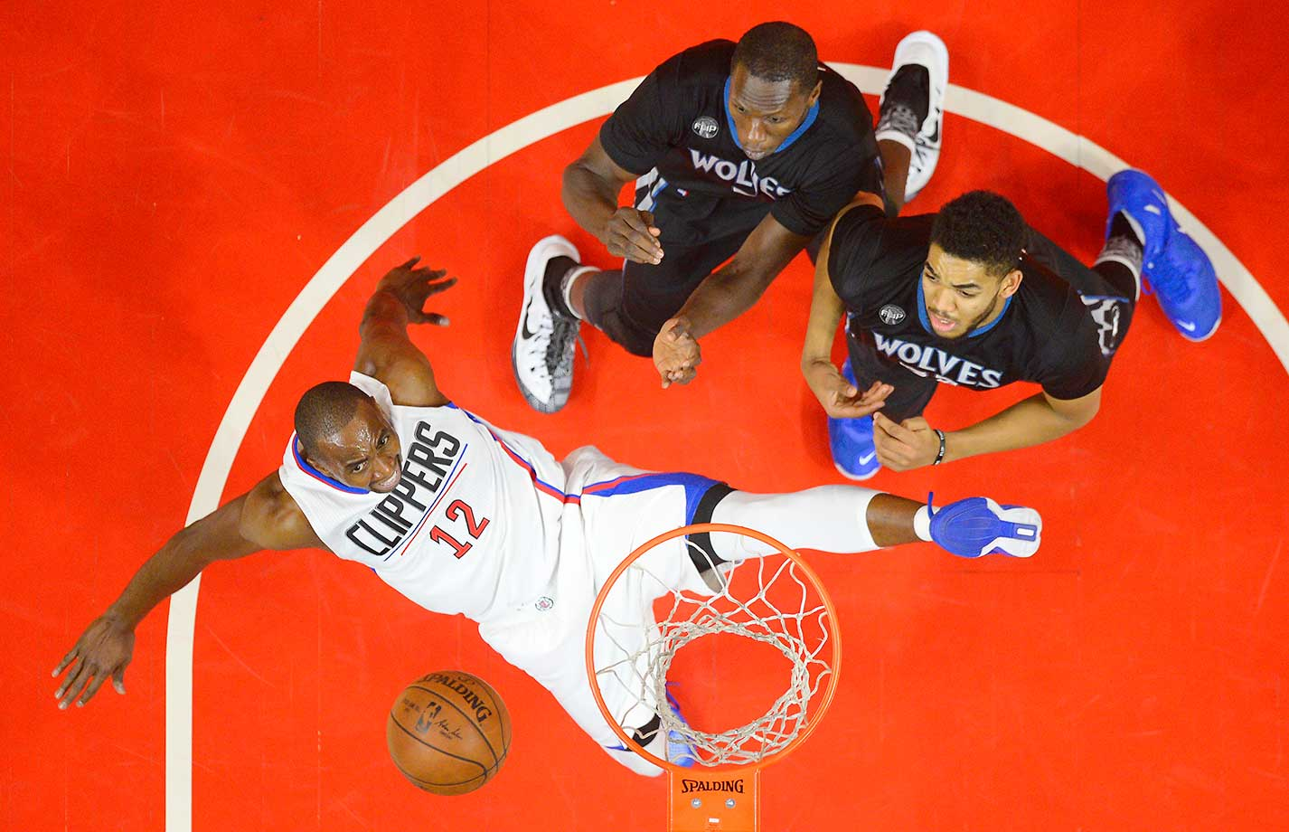 Los Angeles Clippers forward Luc Richard Mbah a Moute falls after shooting as Gorgui Dieng and Karl-Anthony Towns defend in Los Angeles.