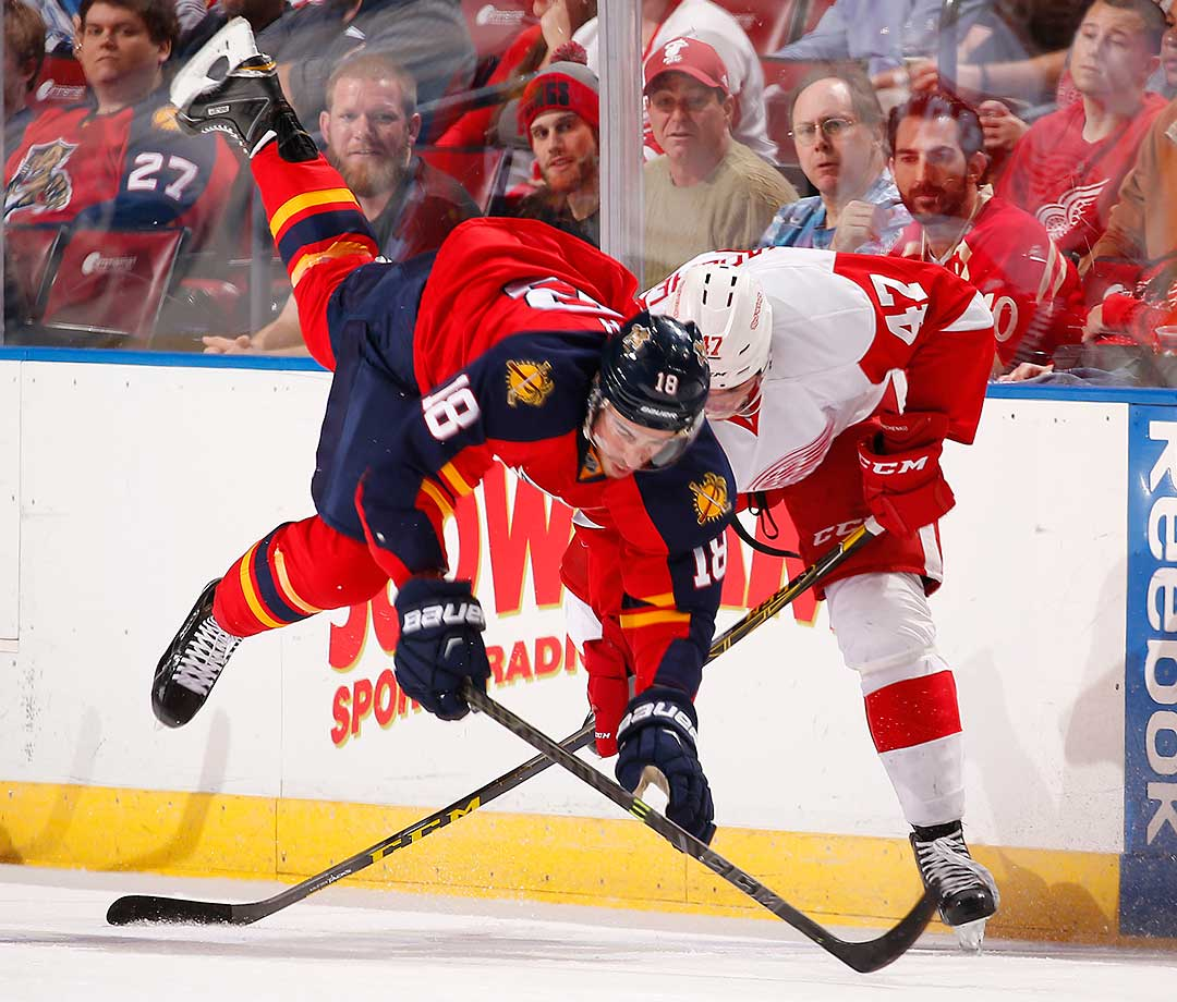 Reilly Smith of the Florida Panthers is tripped up by Alexei Marchenko of the Detroit Red Wings at the BB&T Center in Sunrise, Fla.