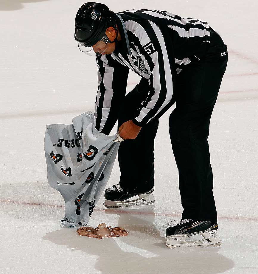 Linesman Jay Sharrers scoops up a octopus during a break in the action between the Detroit Red Wings and the Florida Panthers at the BB&T Center in Sunrise, Fla.