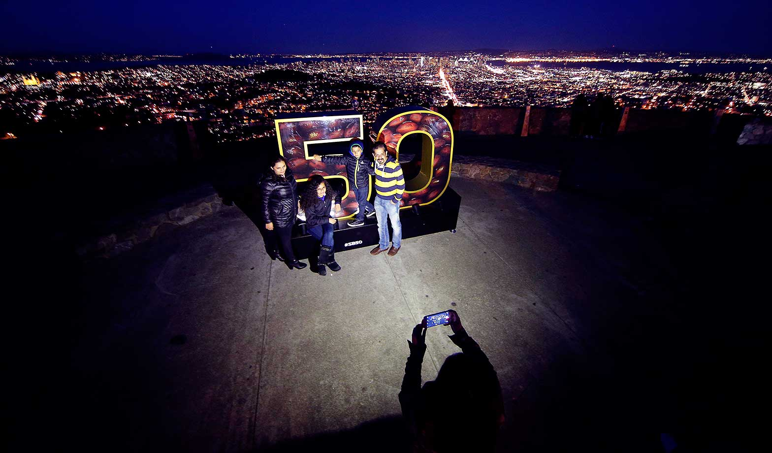 People pose for photos with a Super Bowl 50 sign at Twin Peaks park overlooking San Francisco.