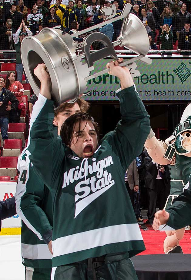 "Michael Ferrantino of Michigan State holds up the new Iron D trophy after the ""Dual in the D"" inaugural game between the Spartans and the Michigan Wolverines at Joe Louis Arena. The Spartans win in 3-2 in overtime."