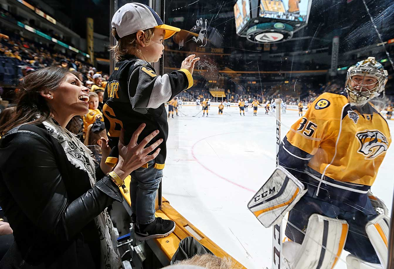 Pekka Rinne of Nashville skates by Beckett Weber and his mom, Bailey, as they watch a game against San Jose.