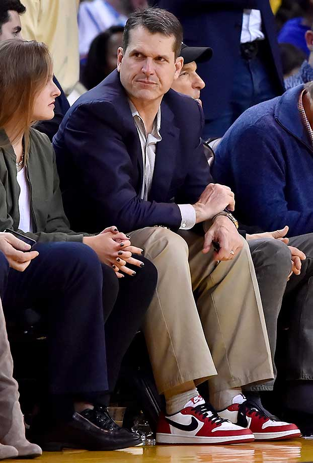 Michigan coach Jim Harbaugh courtside at the Oklahoma City-Golden State game in Oakland.
