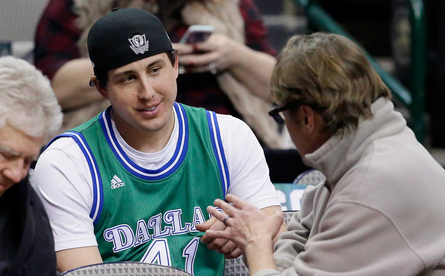 Texas Rangers pitcher Derek Holland sits in the stands before an NBA basketball game between the Minnesota Timberwolves and Dallas Mavericks.