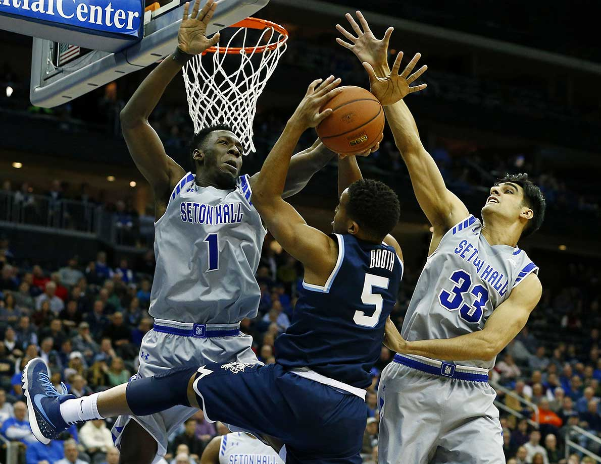 Phil Booth of the Villanova Wildcats attempts a shot as Michael Nzei (1) and Veer Singhof the Seton Hall Pirates defend at the Prudential Center in Newark.