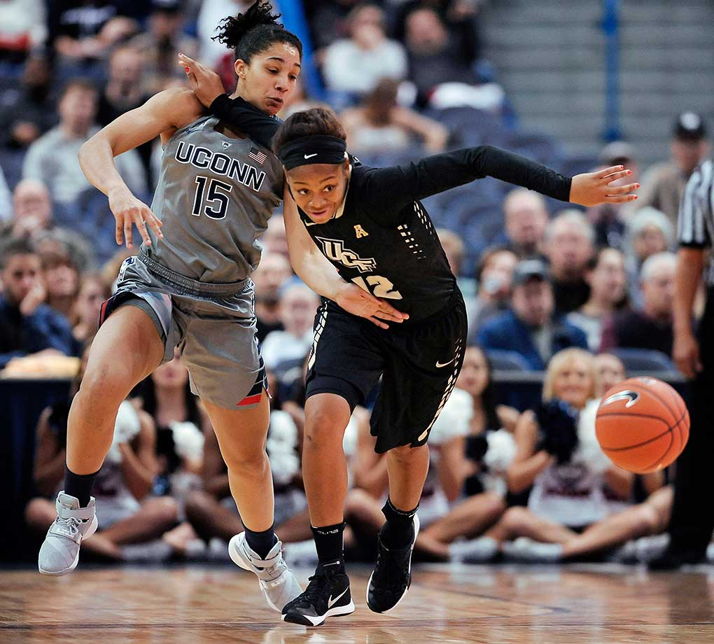 Connecticut's Gabby Williams and UCF's Nyala Shuler chase a loose ball in Hartford, Conn.