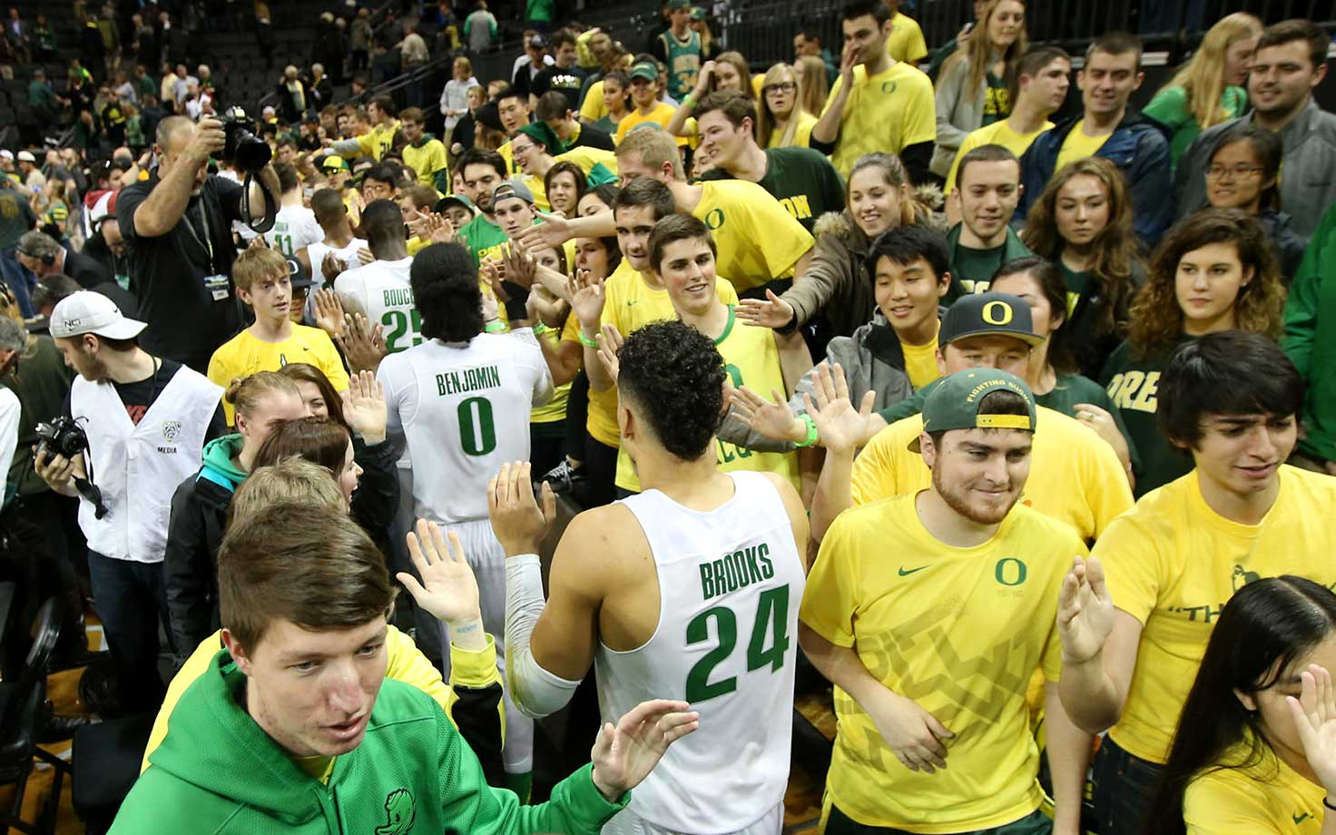 Oregon players, including Dillon Brooks, center, celebrate with student fans after beating Southern California in Eugene, Ore.