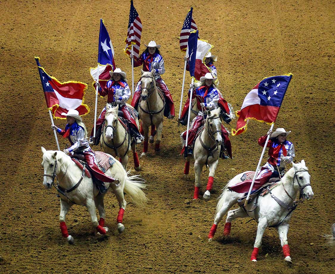 Riders bearing the six flags of Texas enter the arena during the Grand Entry at the Fort Worth Stock Show and Rodeo in Fort Worth.