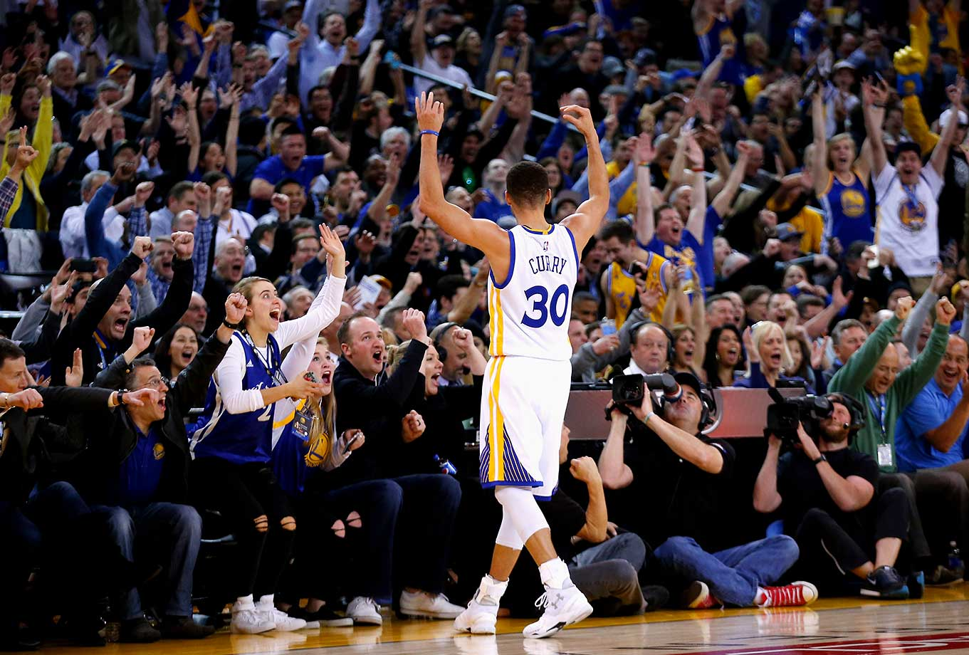 Stephen Curry of the Golden State Warriors reacts after he made a half-court shot to end the first half of their game against the Indiana Pacers at ORACLE Arena in Oakland.