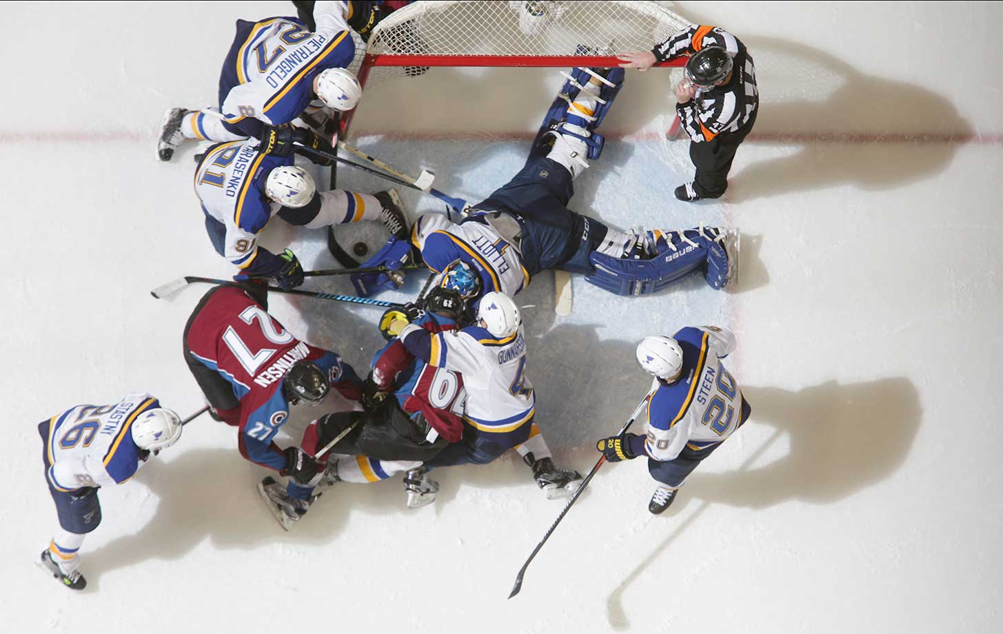 Members of the Colorado Avalanche and the St. Louis Blues surround the Blues net at the Pepsi Center in Denver.