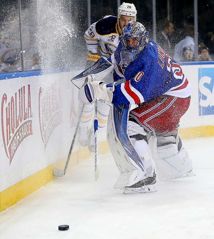 Henrik Lundqvist of the New York Rangers clears the puck as Zemgus Girgensons of the Buffalo Sabres tries to make a play at Madison Square Garden.