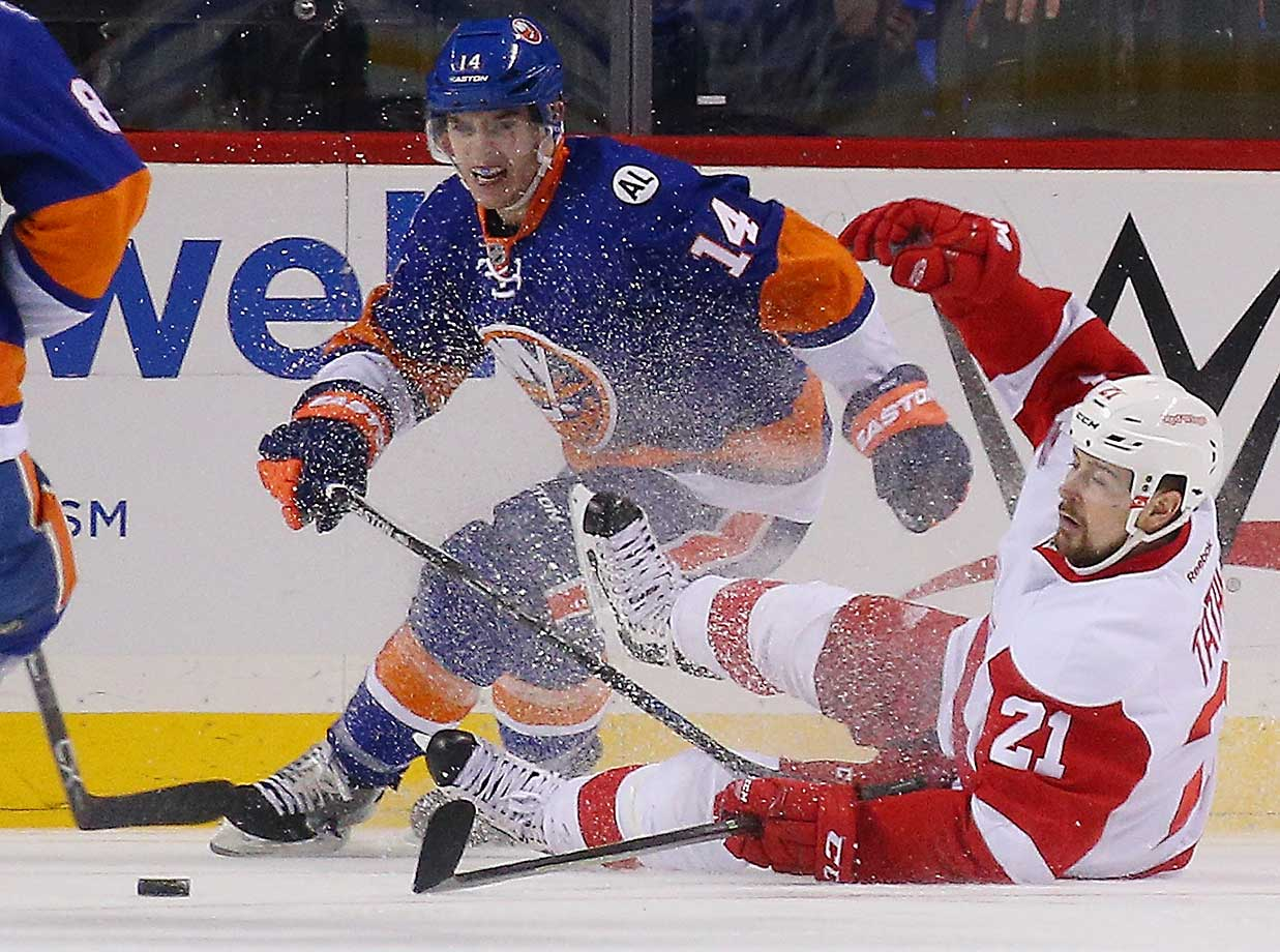 Thomas Hickey of the New York Islanders and Tomas Tatar of the Detroit Red Wings battle for the puck at the Barclays Center.