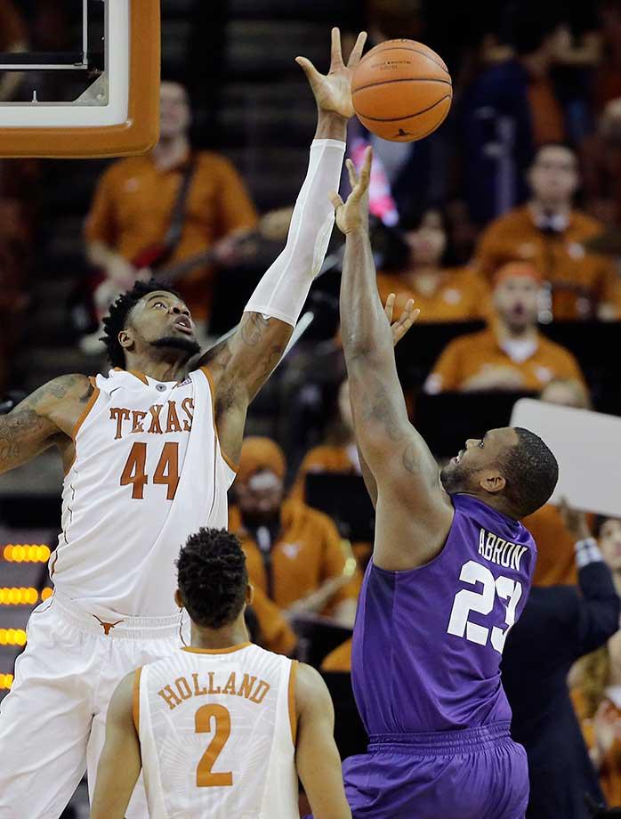 TCU forward Devonta Abron is blocked by Texas center Prince Ibeh as he drives to the basket in Austin, Texas. Texas won 71-54.