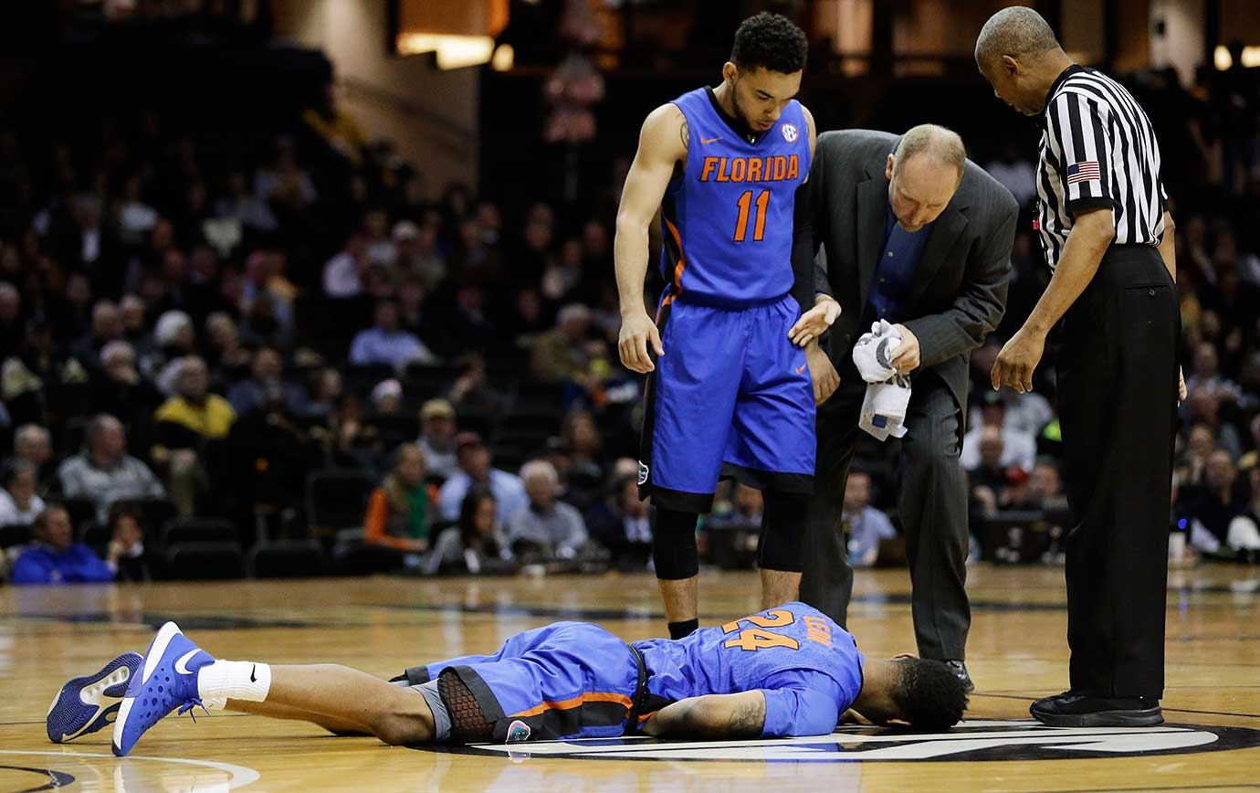 Florida forward Justin Leon lies on the court after being injured against Vanderbilt in Nashville, Tenn. Florida guard Chris Chiozza looks on.
