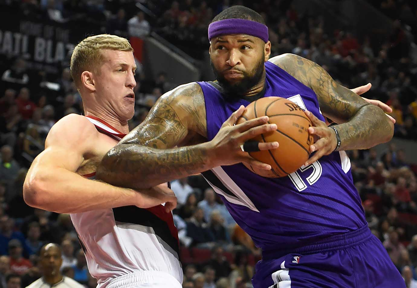 Sacramento Kings center DeMarcus Cousins drives to the basket on Portland Trail Blazers center Mason Plumlee in Portland, Ore.