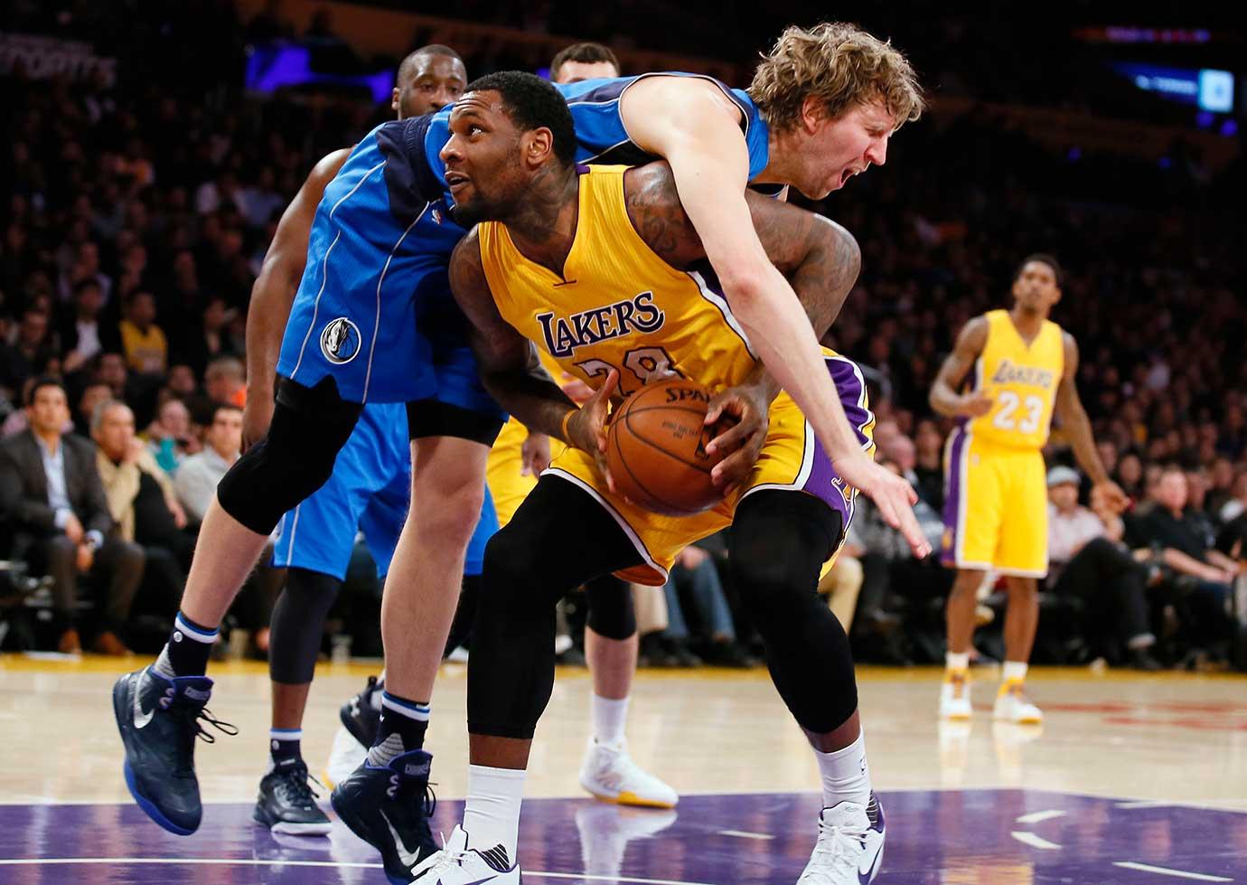 Dirk Nowitzki of Dallas fouls Tarik Black of the Lakers during a game in Los Angeles. The Mavericks won 92-90.