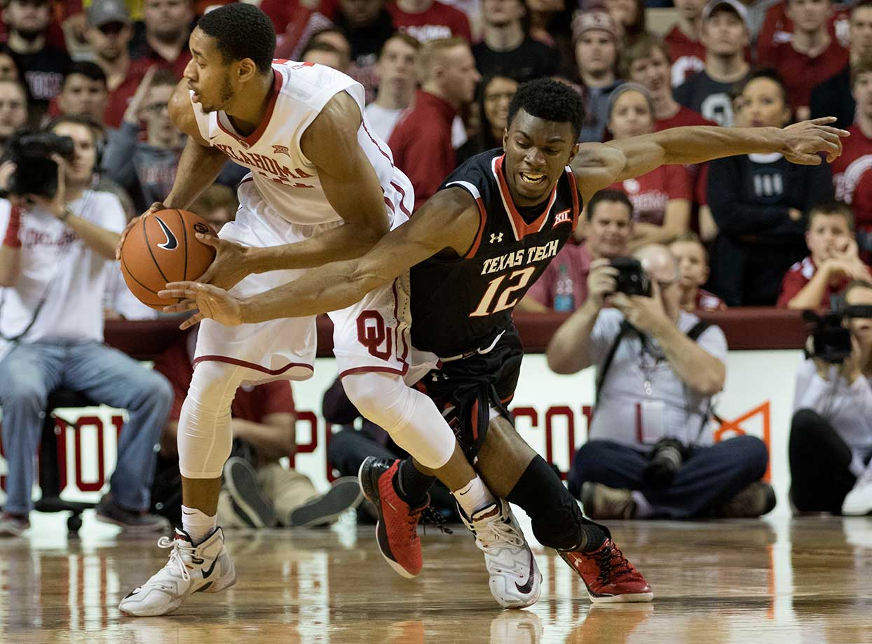 Keenan Evans of the Texas Tech Red Raiders tries to steal the ball from Isaiah Cousins of the Oklahoma Sooners at the Lloyd Noble Center in Norman, Okla.